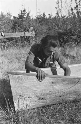 Man carving inside of canoe