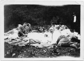 Eight picnickers reclining outdoors
