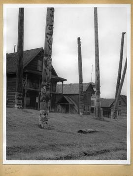 Totem poles in front of buildings