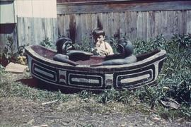 Boy next to carving of canoe and two figures