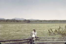 Chilcotin [woman on fence by field]