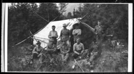 Group portrait of nine men in front of tent