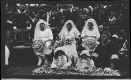 Three brides seated with flowers