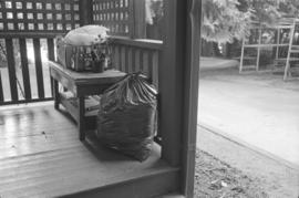 [Full garbage bag next to table on porch]