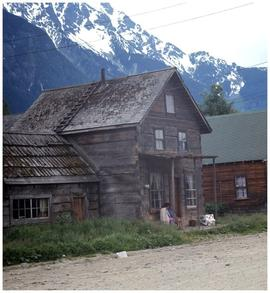 House in unidentified village, with mountains