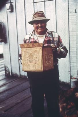 Unidentified man holding carved wooden box