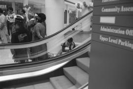 [Tait family members and unidentified person near escalator]