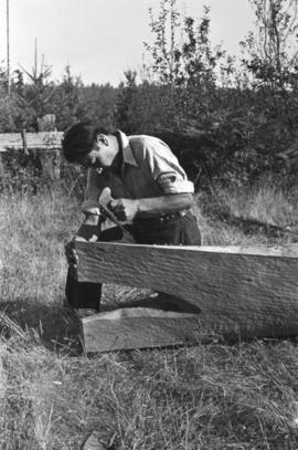 Man carving end of canoe