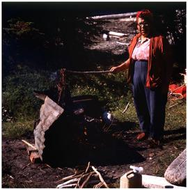 People (Haida) [woman roasting cedar roots]